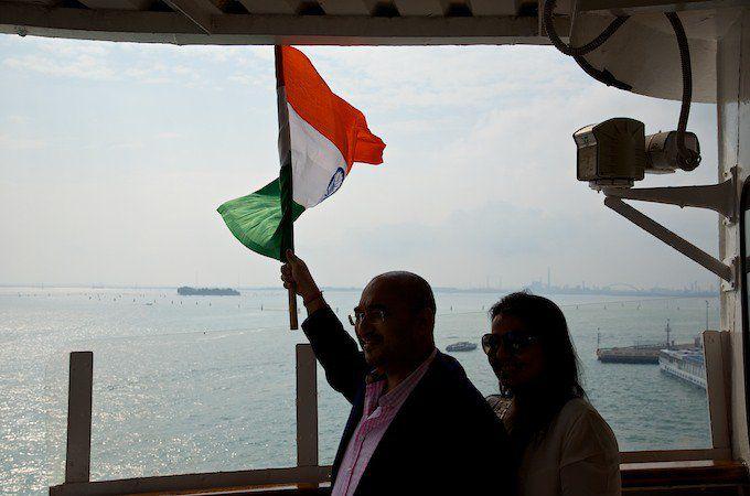Pradeep Agrawalt, der Eigner der MS Delphin schwenkt die indische Flagge beim Auslaufen bei der Jungfernfahrt