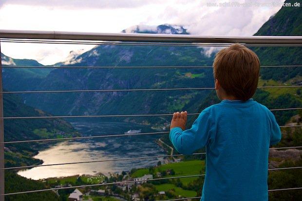 Leon schaut hinab vom Dalsnibba auf den Geiranger Fjord wo die Princess Daphne vor Anker liegt