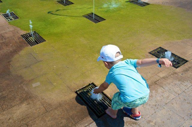 Julian spielt mit den Wasserfontänen an der Strandpromenade in Civitavecchia